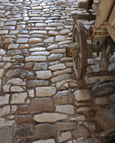 Centuries old cobblestone with old carriage. Medieval cobblestone of urban street and wheel of an old carriage Royalty Free Stock Image