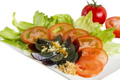 Century egg salad. Plate of green lettuce, sliced red tomatoes and chopped century egg salad Royalty Free Stock Photo