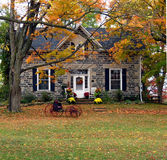 Century Home. A wreath and pots of mums at the front door and an old carriage on the leaf-strewn lawn invite the visitor to welcome autumn royalty free stock photography