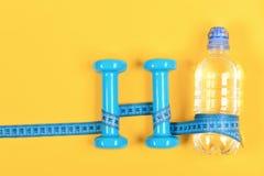 Centymetr zawijający wokoło butelki i dumbbell, odgórny widok obraz royalty free