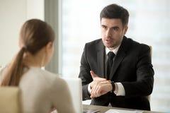 CEO询问女性雇员关于工作延迟原因  免版税库存照片