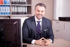 CEO adulto sorridente al suo scrittorio in ufficio Fotografie Stock