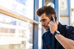 CEO barbudo acertado del varón en traje formal que llama por teléfono vía el teléfono de célula foto de archivo