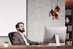 CEO barbuto nel suo ufficio con gli scaffali per libri Immagine Stock