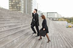 CEO of big company man talking on smartphone and secretary. CEO men talking on smartphone and secretary women go to work, colleagues Americans climbing stairs Stock Photo