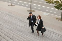 CEO of big company man talking on smartphone and secretary. CEO men talking on smartphone and secretary women go to work, colleagues Americans climbing stairs Stock Images