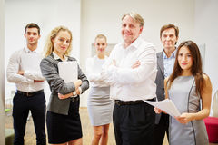 CEO and business team standing with crossed arms Stock Images