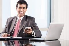 CEO de la compañía en oficina, leyendo el texto en smartphone Fotos de archivo