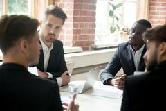 CEO discussing corporate matters with employees in office. CEO discussing corporate matters with group of employees. Boss consulting group of coworkers during stock image