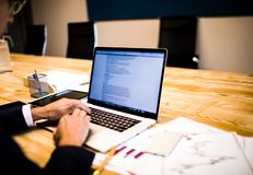 CEO do homem que introduz o texto relativo à promoção no caderno durante o dia do trabalho na empresa Tela de Netbook imagem de stock royalty free