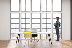 CEO at his workplace with white desk, an office chair and a transparent yellow visitor chair. Large windows are in the background. 3d rendering Royalty Free Stock Photo