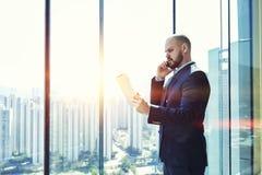 CEO joven del varón que tiene conversación telefónica móvil seria imagen de archivo libre de regalías