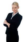 CEO joven sonriente de la hembra que presenta con los brazos plegables Foto de archivo