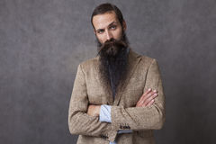 CEO with long beard. Serious businessman with long beard standing against gray background. Concept of CEO royalty free stock photo