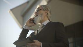 CEO mayor caucásico usando un smartphone y una tableta elegante almacen de metraje de vídeo