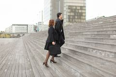 CEO of big company man talking on smartphone and secretary. CEO men talking on smartphone and secretary women go to work, colleagues Americans climbing stairs Stock Photos