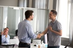 Ceo motivating rewarding male employee shaking hand congratulati