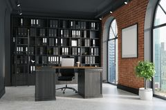 CEO office, bookcase and table. CEO office with brick and black walls, a concrete floor, tall windows and a framed poster. A large table with a laptop is Royalty Free Stock Images