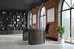 CEO office, bookcase and table, corner. CEO office with brick and black walls, a concrete floor, tall windows and a framed poster. A large table with a laptop is Stock Photography