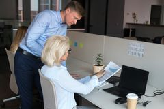 Ceo pointing on financial report having questions talking with employee. Serious company ceo mature businesswoman sitting at desk talking with employee male royalty free stock photography