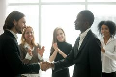 Ceo with team appreciating black manager by handshake and applau