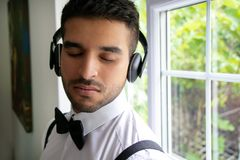 CEO, tragendes Smoking des Geschäftsmannes hört auf Kopfhörer mit geschlossenen Augen lizenzfreies stockbild