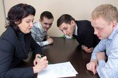 CEO und drei hörende Arbeitskräfte Stockfotos