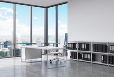 A CEO workplace in a modern corner panoramic office in New York city. A white desk with a laptop, white leather chair and a booksh Royalty Free Stock Image