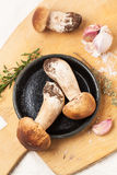 Cep mushrooms with garlic. Top view on cep mushrooms with thyme and garlic served on wooden cutting board Stock Photo