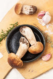 Cep mushrooms with garlic. Top view on cep mushrooms with thyme and garlic served on wooden cutting board Stock Photography