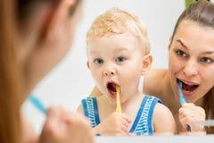 Cepillado de dientes de enseñanza del niño de la madre imagen de archivo libre de regalías