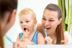 Cepillado de dientes de enseñanza del niño de la madre fotografía de archivo