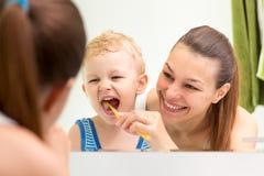 Cepillado de dientes de enseñanza del niño de la madre fotografía de archivo libre de regalías