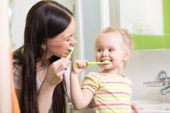 Cepillado de dientes de enseñanza del niño de la mamá linda Foto de archivo