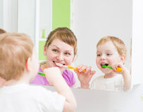 Cepillado de dientes feliz de la madre y del niño en cuarto de baño Imagenes de archivo