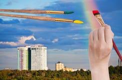 Cepille el arco iris de las pinturas en nubes azules sobre casas Imágenes de archivo libres de regalías