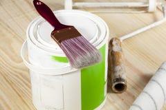 Cepille la colocación en una lata de la pintura a un lado de un rodillo en un piso de madera Fotografía de archivo