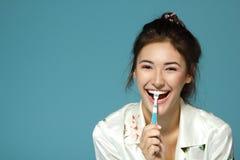 Cepillo adolescente divertido feliz de la muchacha sus dientes Tema de la mañana Foto de archivo