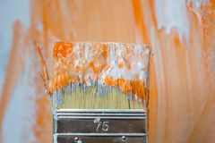 Cepillo con la pintura anaranjada y blanca como la renovación y creación imagen de archivo