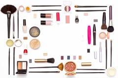 Cepillo cosmético del maquillaje, esmalte de uñas, polvo, rimel, y otros accesorios en un fondo blanco Imagen de archivo