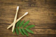 Cepillo de dientes de bambú del cuarto de baño del concepto menos plástico inútil cero del uso y hoja verde en fondo rústico foto de archivo