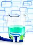 Cepillo de dientes con goma y enjuague sobre el vidrio Foto de archivo libre de regalías