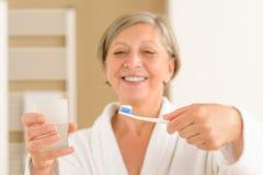 Cepillo de dientes del asimiento de la mujer y agua mayores del vidrio foto de archivo