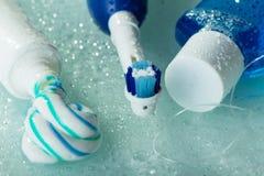 Cepillo de dientes eléctrico, goma y enjuague, en estante de cristal mojado Foto de archivo