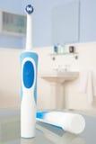 Cepillo de dientes eléctrico y crema dental Imagen de archivo
