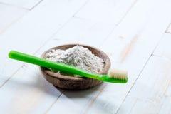 Cepillo de dientes verde y sal ecológica del bicarbonato de sosa en taza de madera Fotos de archivo