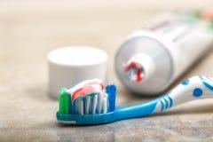 Cepillo de dientes y crema dental en el estante Imagen de archivo