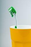 Cepillo de dientes y taza Fotos de archivo