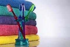 Cepillo de dientes y toallas de baño fotos de archivo