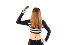 Cepillo de la tenencia de la mujer cerca de su pelo Imagenes de archivo